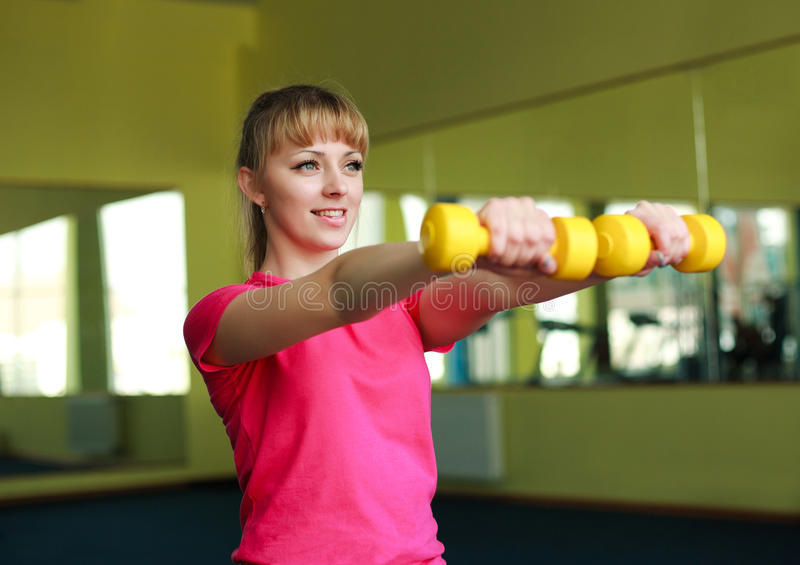 Muchacha deportiva que hace ejercicio con pesas de gimnasia imagenes de archivo