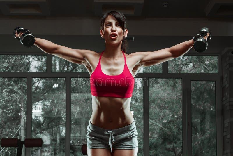 Muchacha deportiva que hace ejercicio con pesas de gimnasia foto de archivo