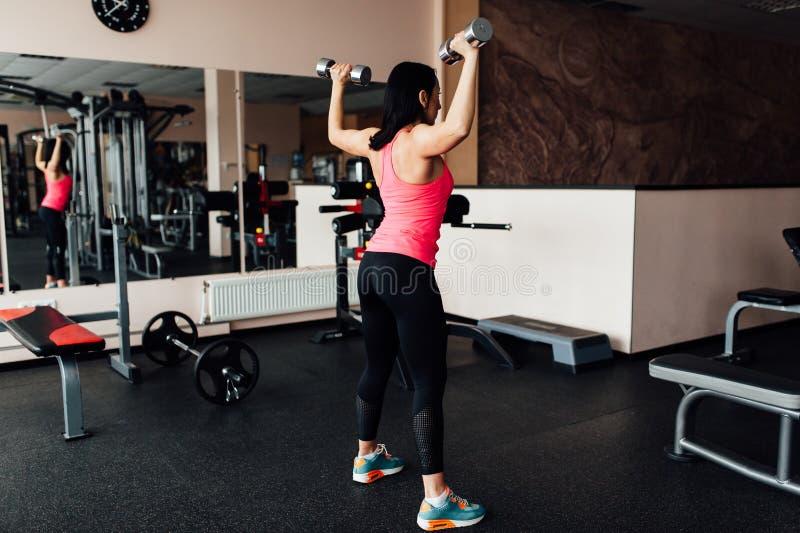 Muchacha deportiva que hace ejercicio con pesas de gimnasia fotos de archivo libres de regalías