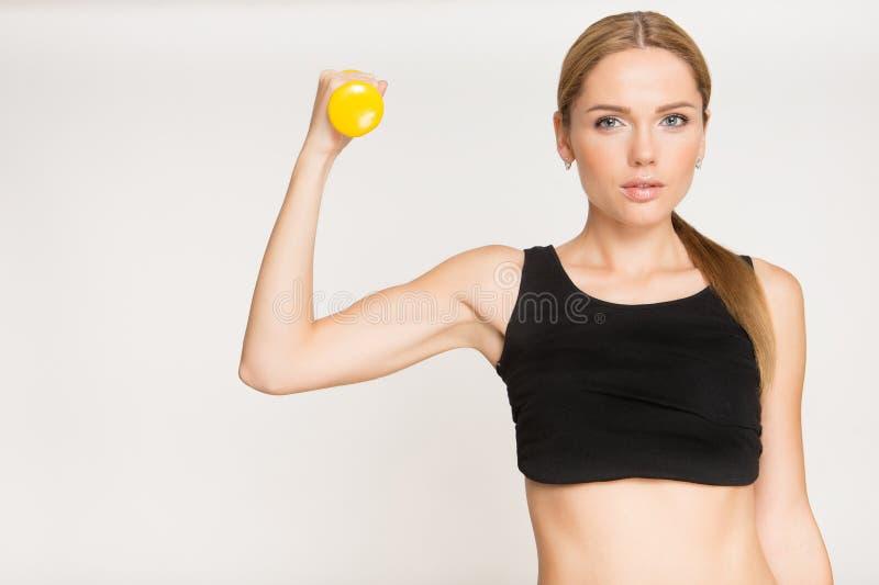 Muchacha deportiva que hace ejercicio con pesas de gimnasia y que mira la cámara imagenes de archivo