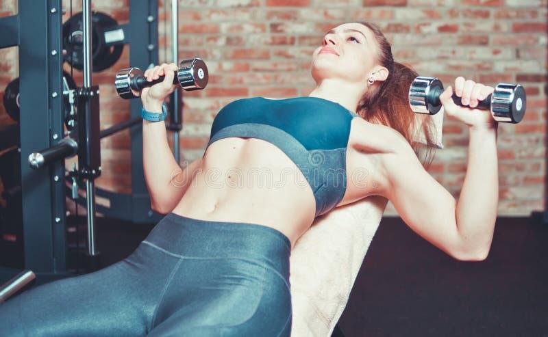 Muchacha deportiva que hace la prensa de la pesa de gimnasia imagenes de archivo