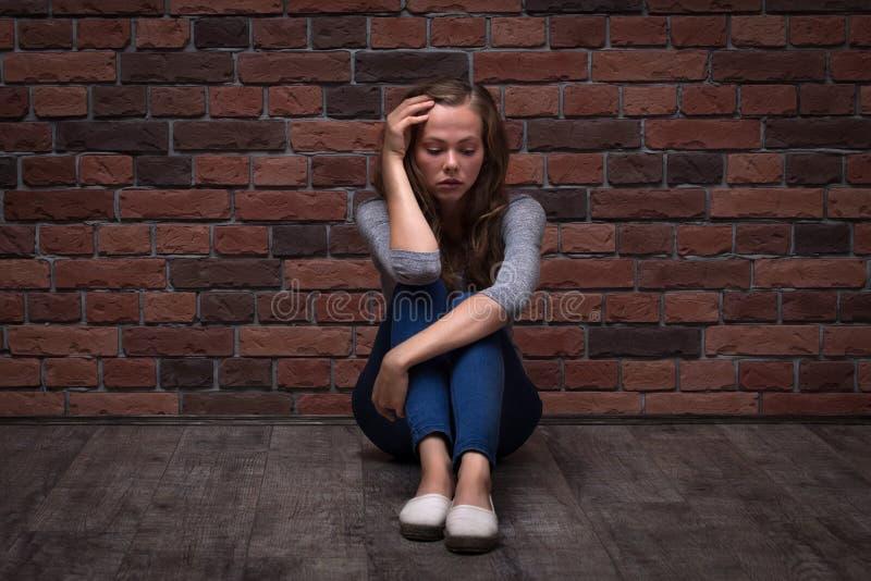 Muchacha deprimida del adolescente que se sienta solamente en el piso en el cuarto oscuro imagen de archivo