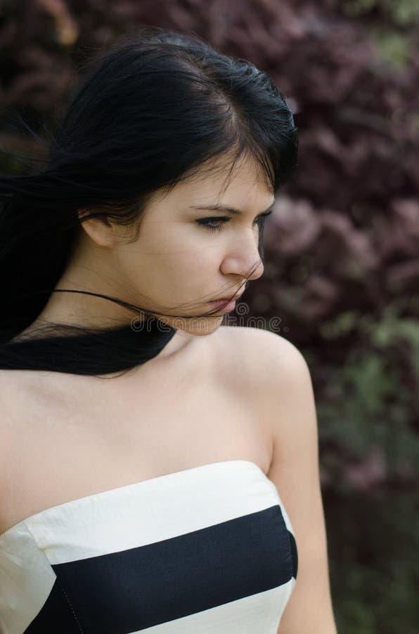 Muchacha deprimida hermosa que se coloca al aire libre en día ventoso fuerte imagenes de archivo