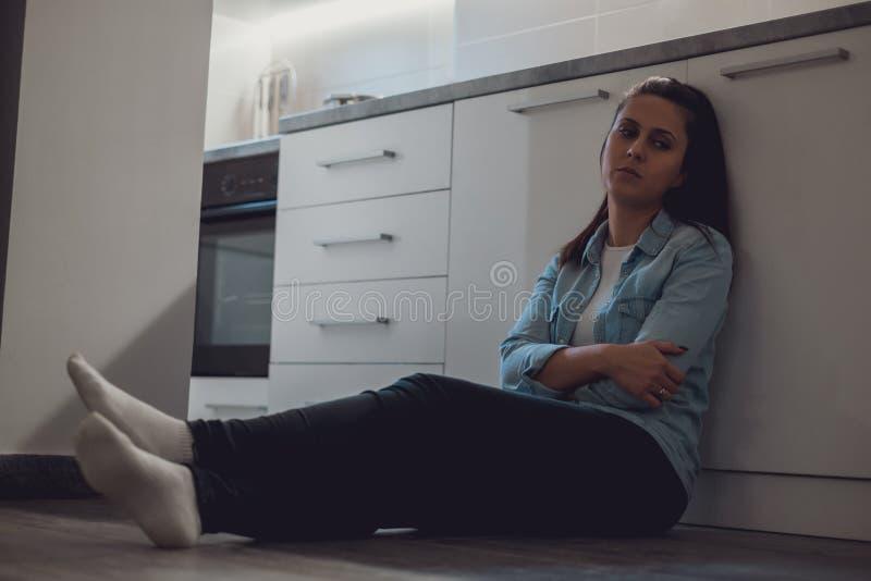 Muchacha deprimida que se sienta en el piso de la cocina foto de archivo