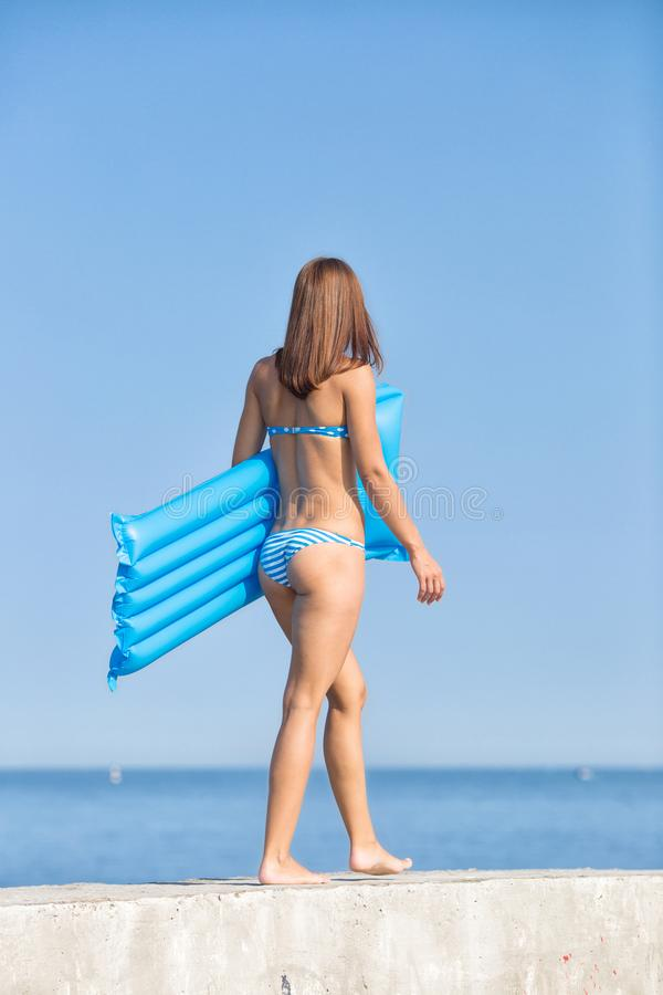 Muchacha descalza en bikini azul en el mar foto de archivo