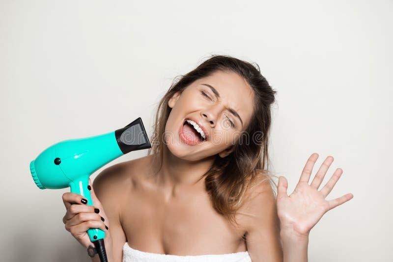 Muchacha desnuda hermosa joven en toalla que canta con el hairdryer imagen de archivo libre de regalías