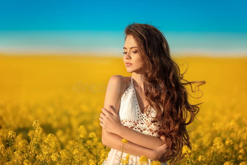 Muchacha despreocupada hermosa con el pelo sano rizado largo sobre fondo amarillo del paisaje del campo de la violación Morenita  imágenes de archivo libres de regalías