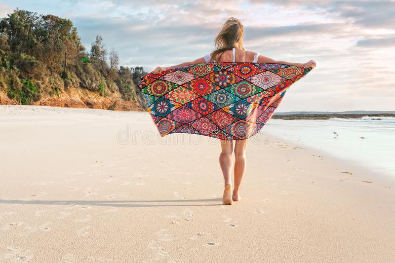Muchacha despreocupada que camina a lo largo de la madrugada de la playa foto de archivo libre de regalías