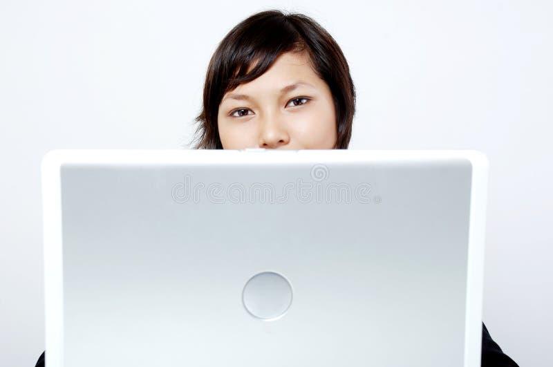 Muchacha detrás de la computadora portátil fotos de archivo