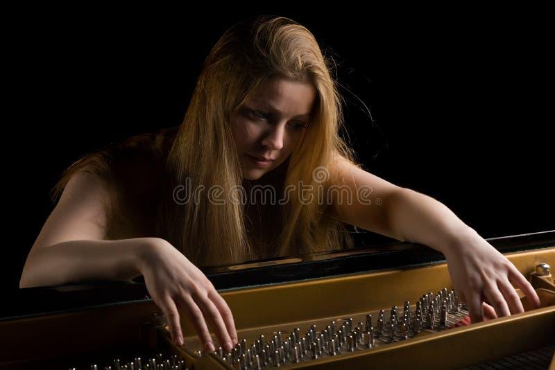 Muchacha detrás de un piano magnífico imagenes de archivo