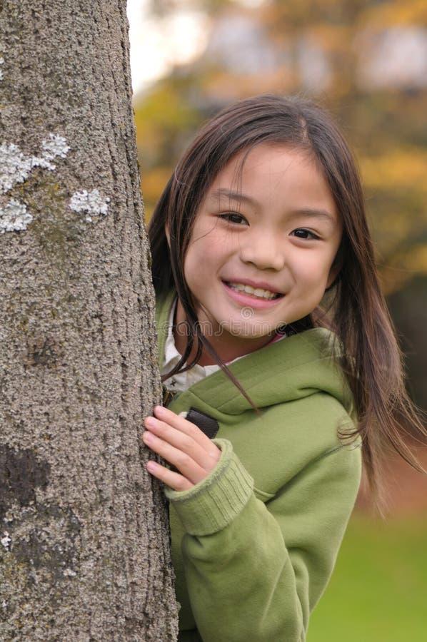Muchacha detrás del árbol imagen de archivo libre de regalías