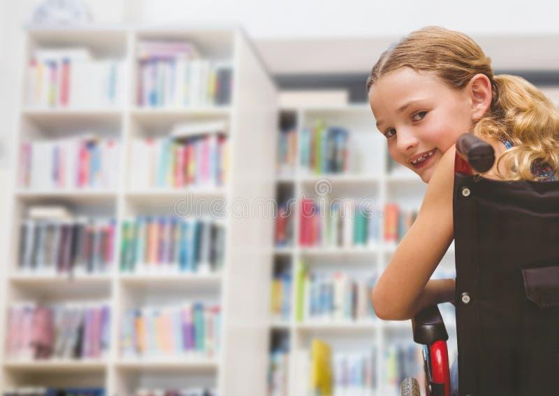 Muchacha discapacitada en silla de ruedas en biblioteca escolar fotos de archivo libres de regalías