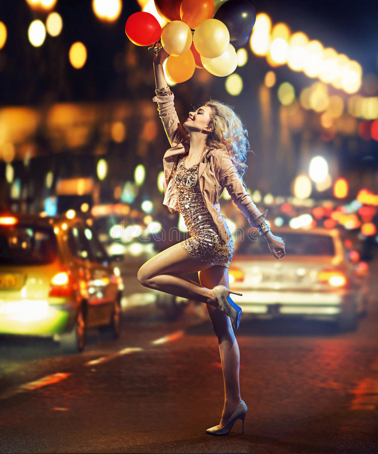 muchacha Diversión-cariñosa que sostiene un manojo de globos fotografía de archivo