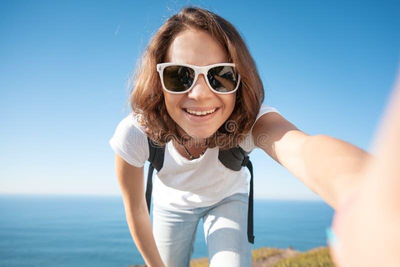 Muchacha divertida atractiva joven en una camiseta blanca y vaqueros contra foto de archivo