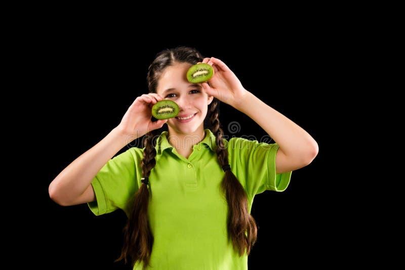 Muchacha divertida con el kiwi cortado en ojos fotos de archivo