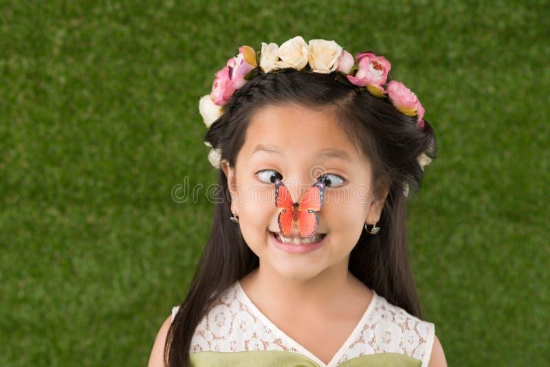 Muchacha divertida con la mariposa en nariz imagen de archivo