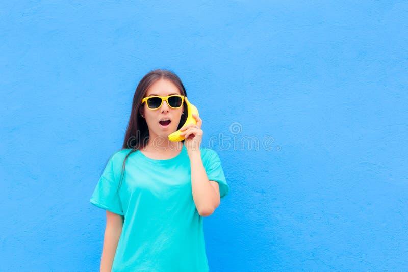 Muchacha divertida con las gafas de sol y el teléfono del plátano en fondo azul imágenes de archivo libres de regalías