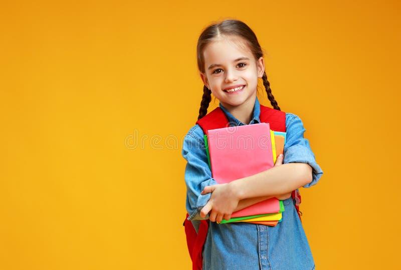 Muchacha divertida de la colegiala del niño en fondo amarillo imagen de archivo libre de regalías