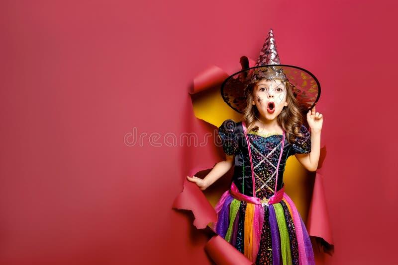 Muchacha divertida de risa del niño en un traje de la bruja en Halloween imagenes de archivo