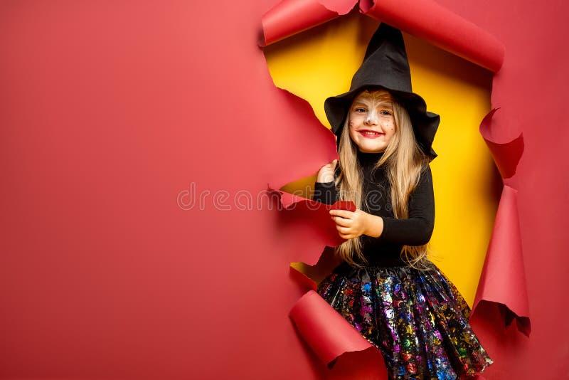 Muchacha divertida de risa del niño en un traje de la bruja en Halloween fotografía de archivo