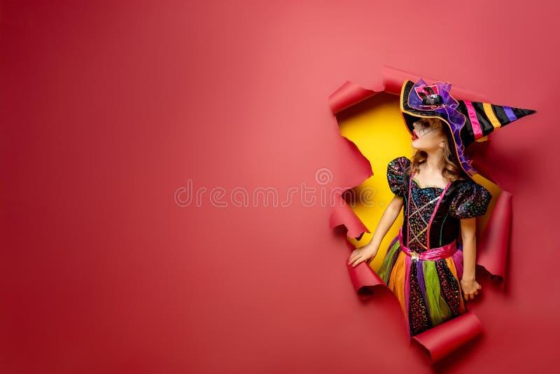 Muchacha divertida de risa del niño en un traje de la bruja en Halloween fotos de archivo