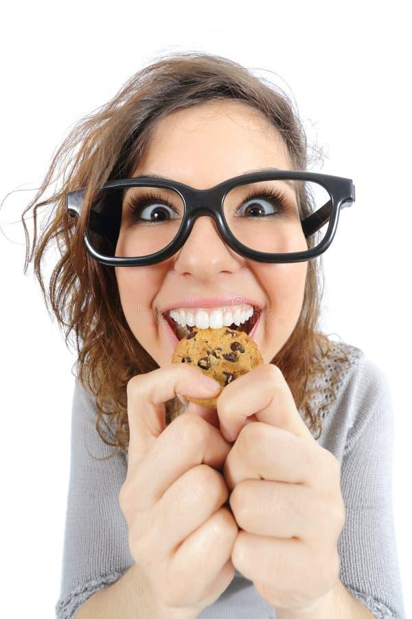 Muchacha divertida del friki que come una galleta foto de archivo libre de regalías