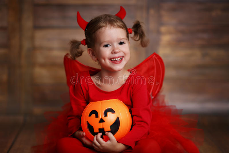 Muchacha divertida del niño en el traje de Halloween del diablo en la parte posterior de madera oscura imagenes de archivo