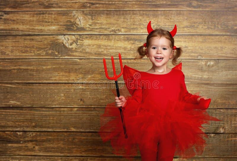Muchacha divertida del niño en el traje de Halloween del diablo en la parte posterior de madera oscura imágenes de archivo libres de regalías
