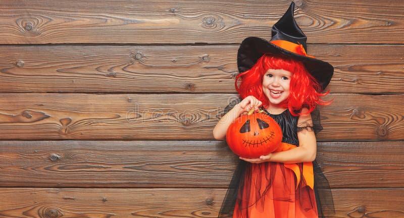 Muchacha divertida del niño en el traje de la bruja para Halloween con la calabaza Ja fotos de archivo