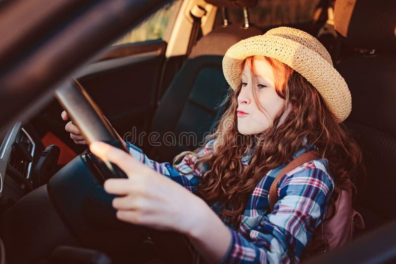 muchacha divertida del niño que juega el conductor, sentándose en asiento delantero imagen de archivo