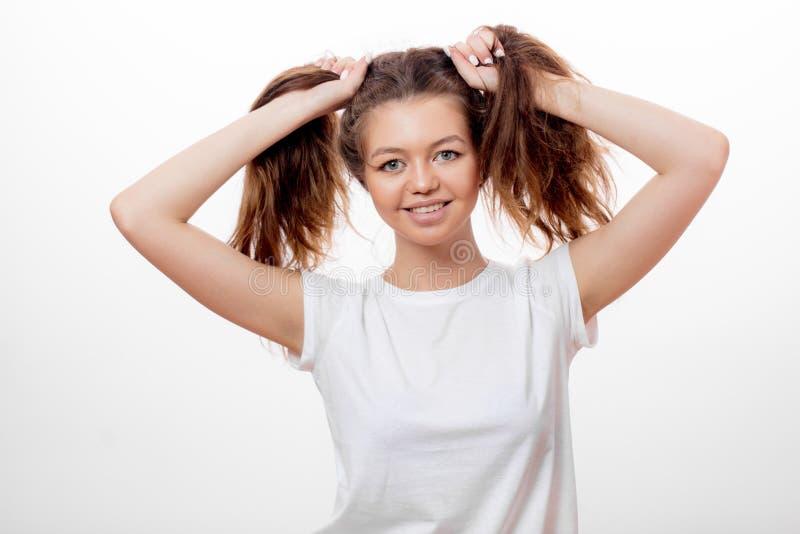 Muchacha divertida en la camiseta blanca que hace dos colas de caballo con su pelo marrón imágenes de archivo libres de regalías