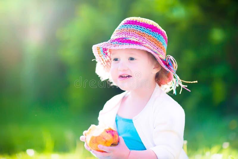 Muchacha divertida en un sombrero que come la manzana fotografía de archivo libre de regalías