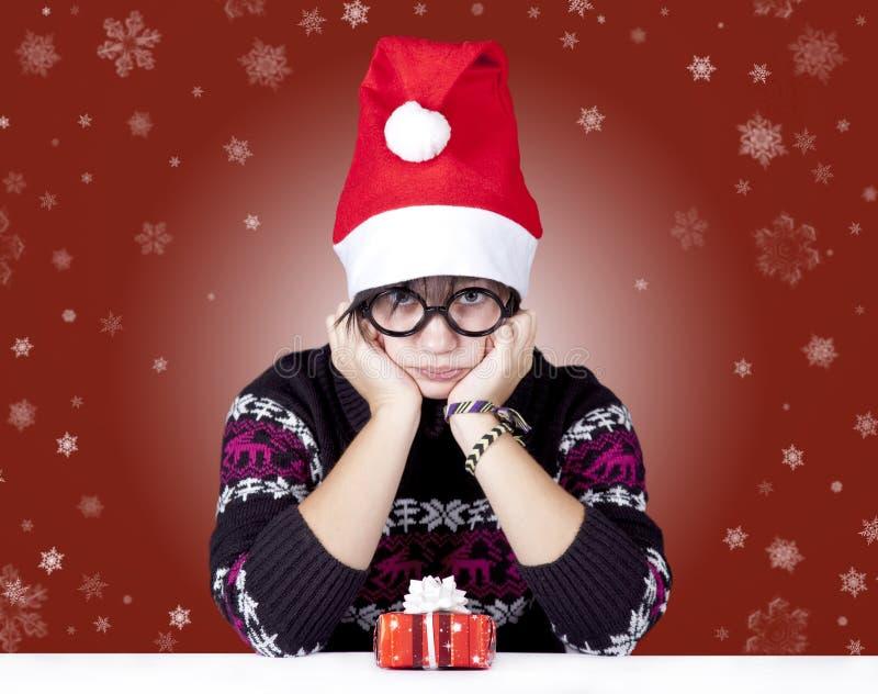 Muchacha divertida en vidrios con los regalos de la Navidad. imagenes de archivo