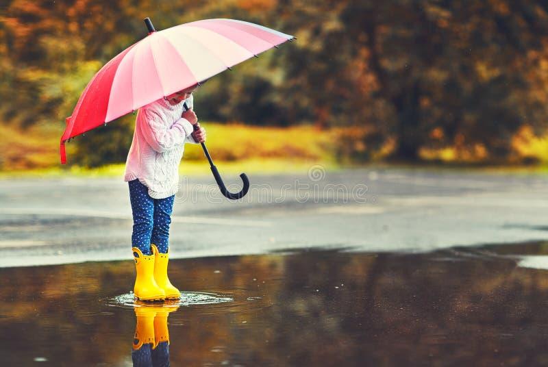 Muchacha divertida feliz del niño con el paraguas que salta en charcos en rubb fotos de archivo