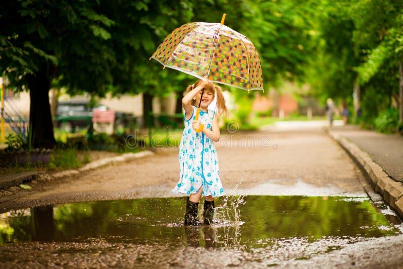Muchacha divertida feliz del niño con el paraguas que salta en charcos en las botas de goma y en vestido del lunar fotografía de archivo