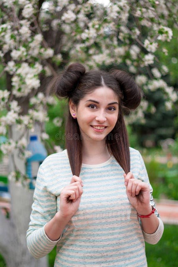 Muchacha divertida hermosa joven Una mujer con una sonrisa hermosa y una mirada coqueta Una muchacha morena joven con los ojos he fotos de archivo libres de regalías