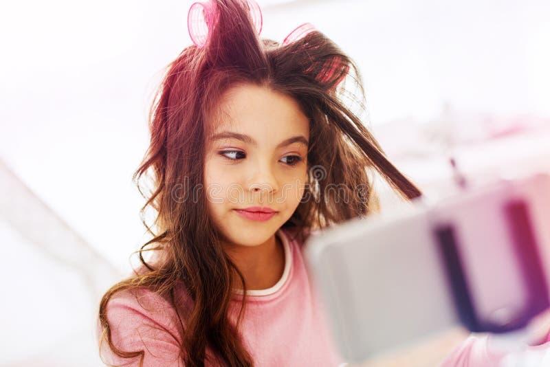 Muchacha divertida linda que siente alegre mientras que hace el peinado en sus el propio en casa foto de archivo