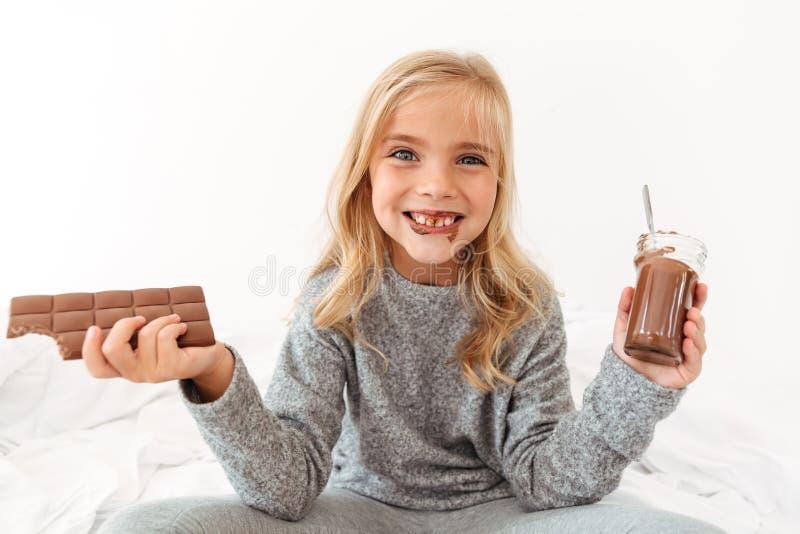 Muchacha divertida linda que sostiene la barra de chocolate y que muestra a su Teet sucio foto de archivo