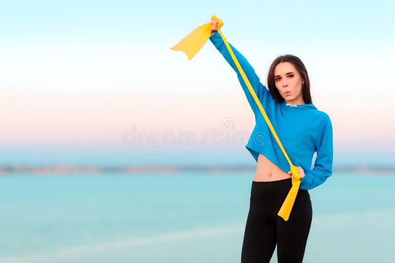 Muchacha divertida que intenta resolverse con la banda de la yoga imagen de archivo