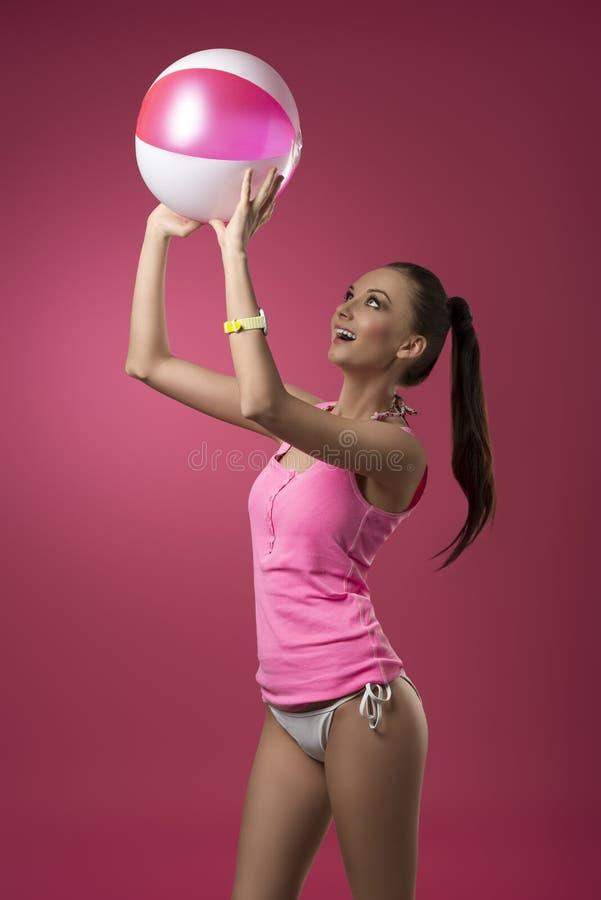 Muchacha divertida que juega con la pelota de playa fotografía de archivo