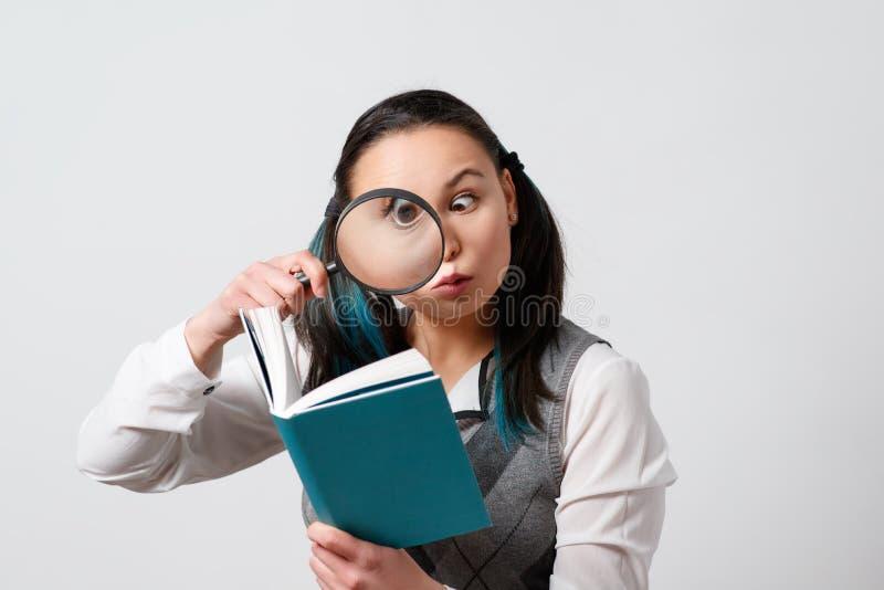 Muchacha divertida que mira un libro a través de una lupa En un fondo gris imagen de archivo