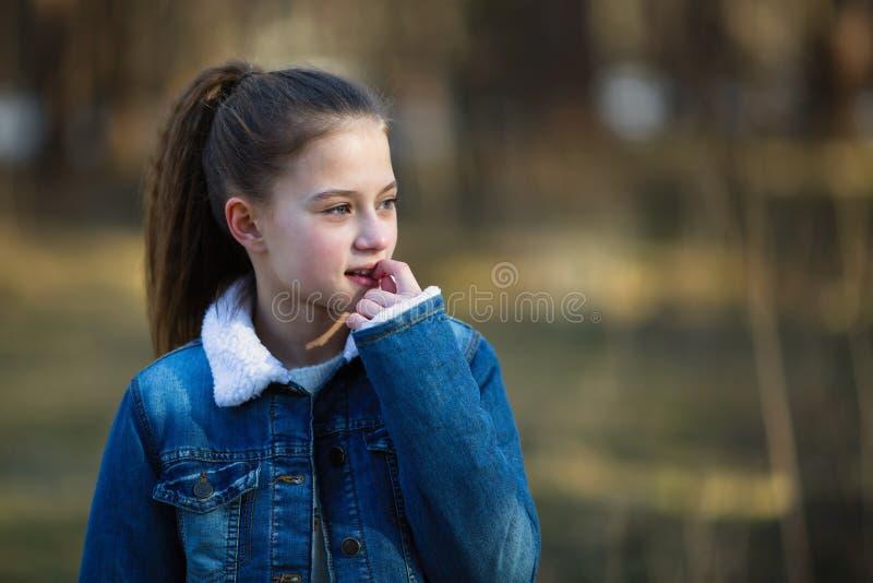 muchacha Doce-año-vieja en una chaqueta del dril de algodón que presenta en un parque del pino fotos de archivo