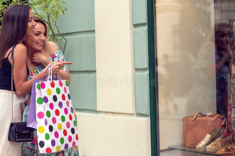 Muchacha dos en las compras que miran la ventana de la tienda en la ciudad imágenes de archivo libres de regalías