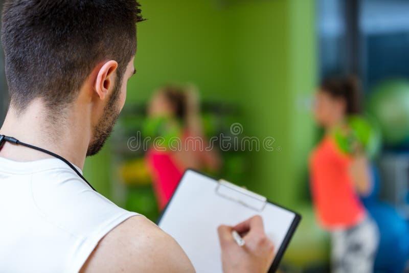 Muchacha dos que ejercita en el gimnasio con un instructor personal foto de archivo libre de regalías