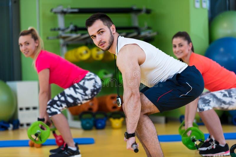 Muchacha dos que ejercita en el gimnasio con un instructor personal imagenes de archivo