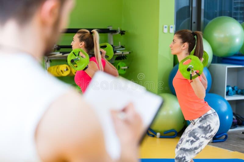 Muchacha dos que ejercita en el gimnasio con un instructor personal fotos de archivo