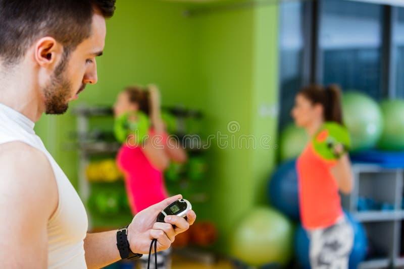Muchacha dos que ejercita en el gimnasio con un instructor personal fotografía de archivo libre de regalías