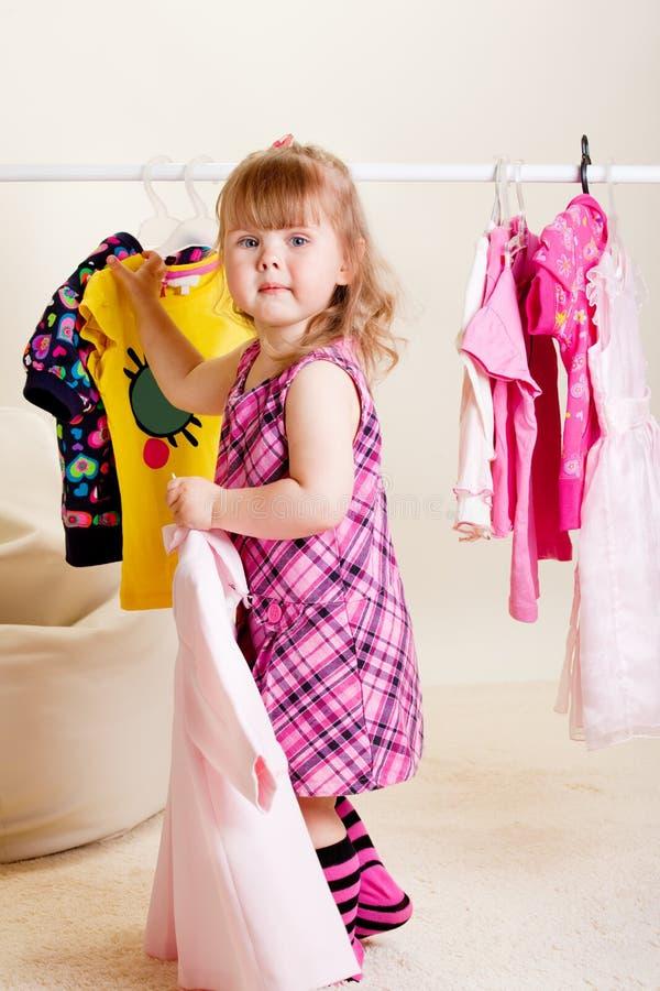 Muchacha dulce que intenta en la ropa fotografía de archivo libre de regalías