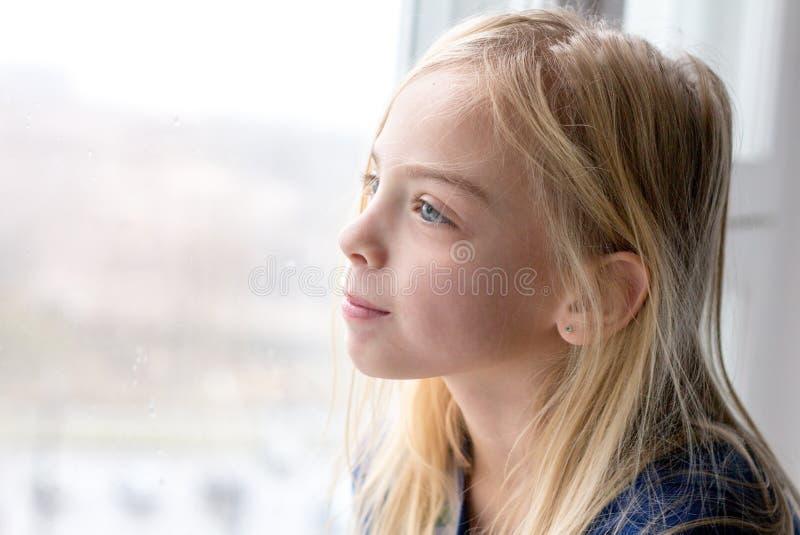 Muchacha dulce que se sienta por la ventana fotos de archivo