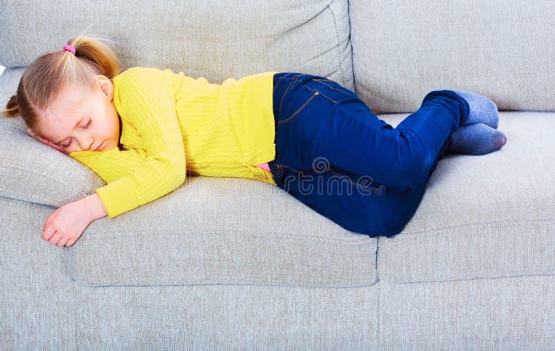 Muchacha durmiente en el sofá imagenes de archivo